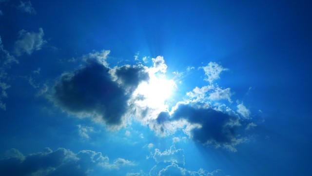 Blå himmel, sol och moln