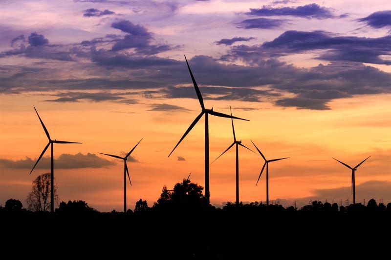 Vindkraftverk mot ljus kvällshimmel